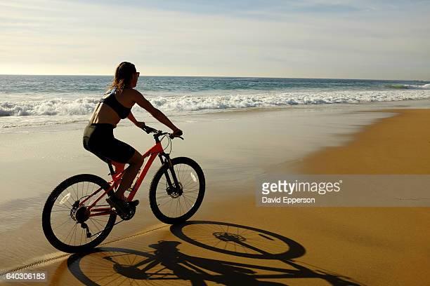 woman biking on beach in california - ブラトップ ストックフォトと画像