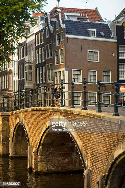 woman biking onto bridge crossing prinsengracht - merten snijders stock pictures, royalty-free photos & images
