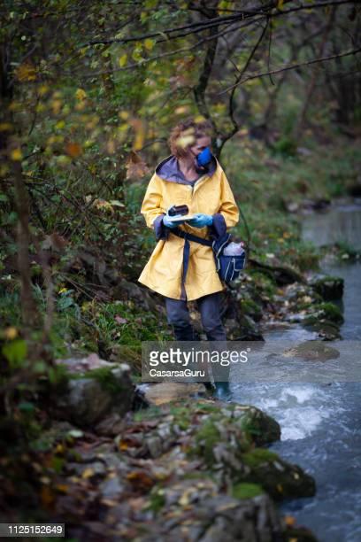 biólogos mulher verificar a pureza da água - desastre ecológico - fotografias e filmes do acervo