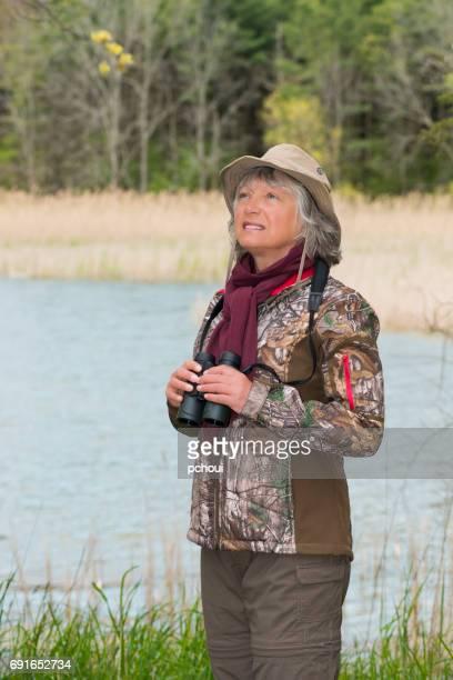 Woman birding, bird watching, active senior