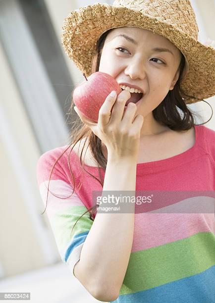 A woman biting an apple