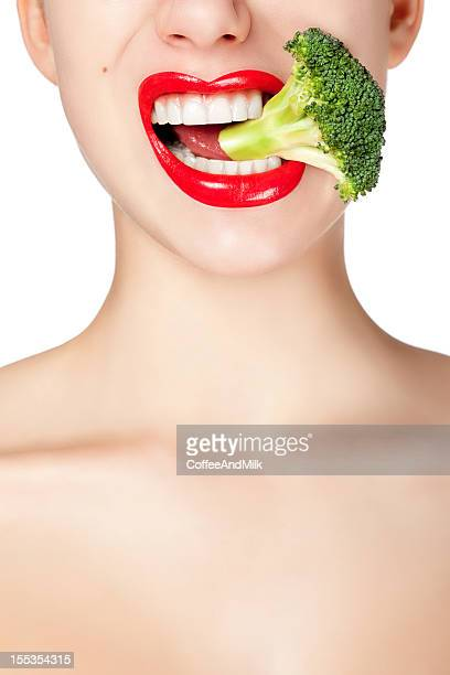 Woman biting broccoli