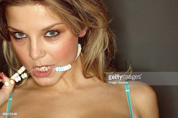 Woman biting candy necklace