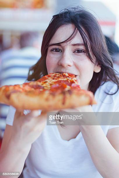 Woman biting in pizza slice
