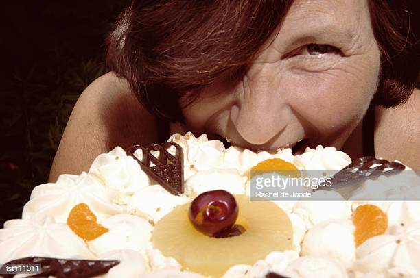 Woman biting into a cake