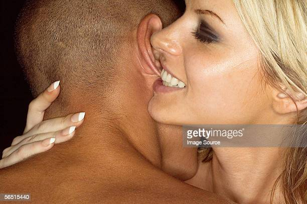 Woman biting mans ear