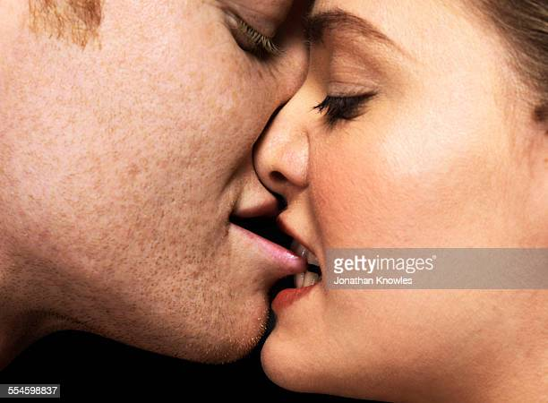 woman biting man's lips, close up - erotiek stockfoto's en -beelden