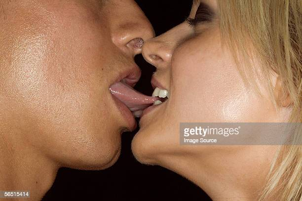 woman biting mans tongue - couple tongue kissing stock photos and pictures