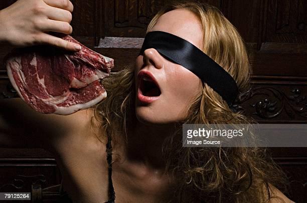 Woman biting raw meat