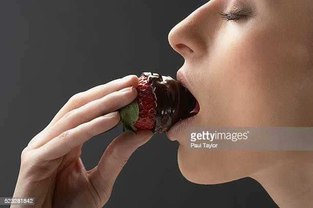Woman bitting chocolate covered strawberry