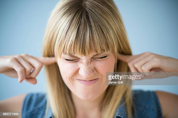 Woman blocking ears with fingers