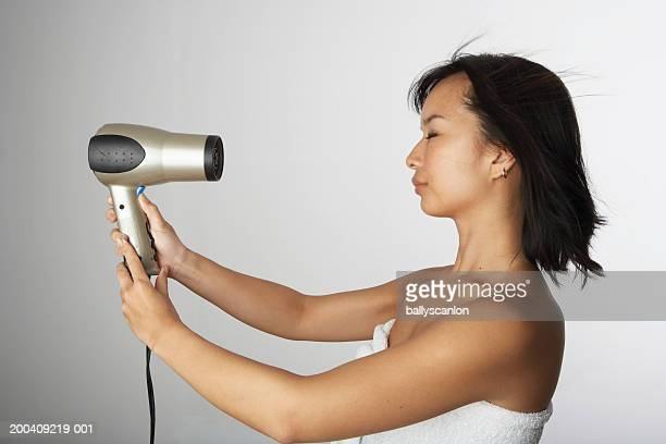Woman blow drying hair in bath towel