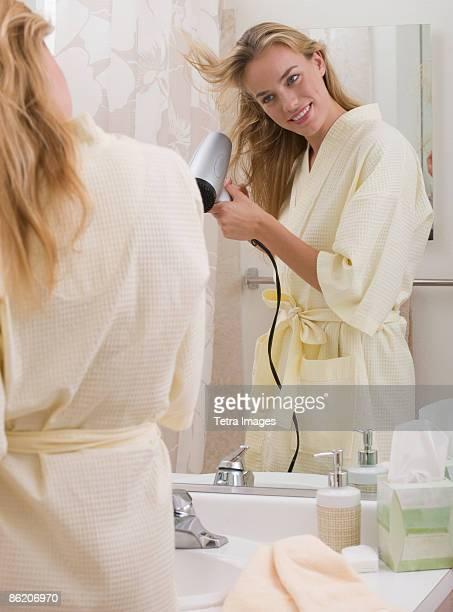 Woman blow-drying hair in bathroom