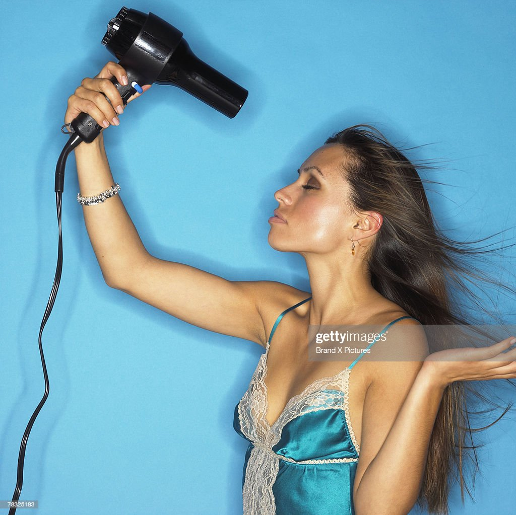 Woman blow-drying her hair : Stock Photo