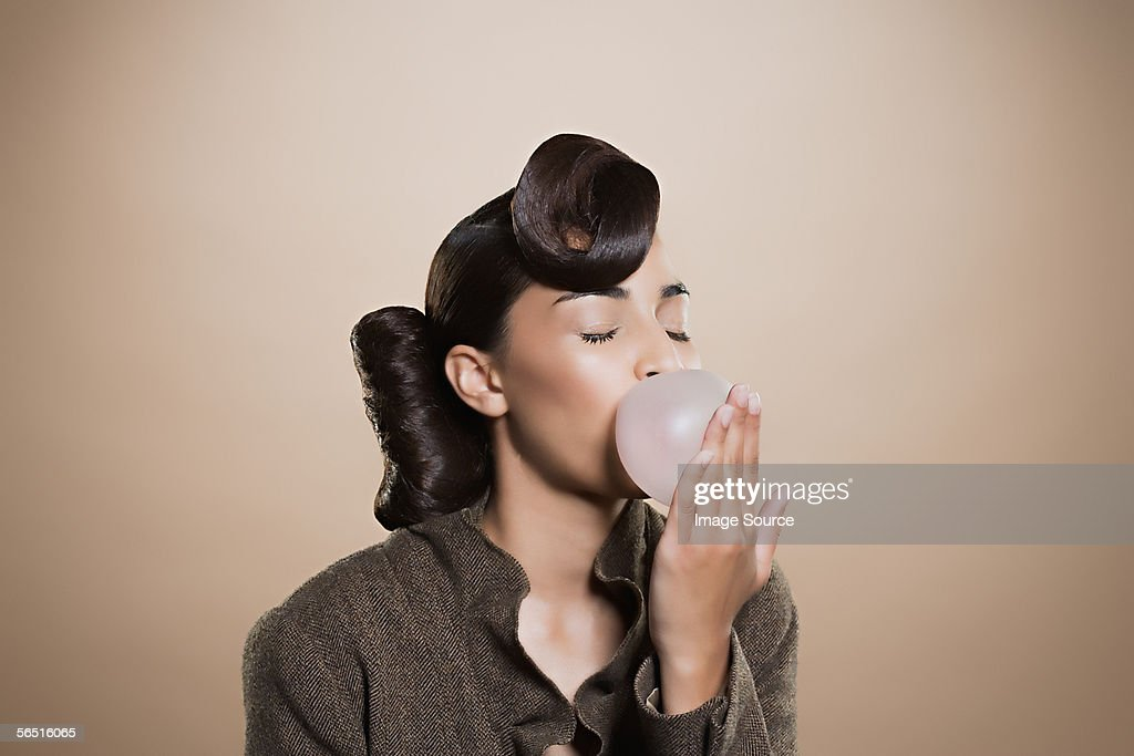 Woman blowing a bubble gum bubble : Stock Photo