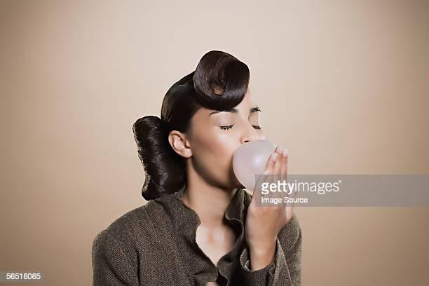 Woman blowing a bubble gum bubble