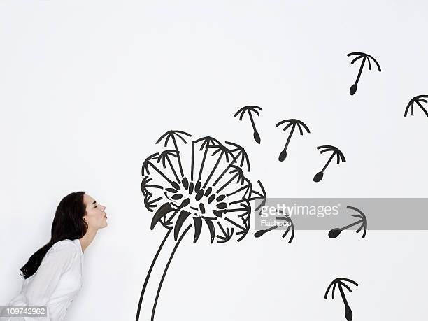 Woman blowing a dandelion clock