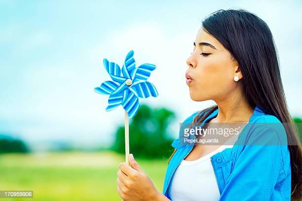 Frau weht ein Windrad in der Natur