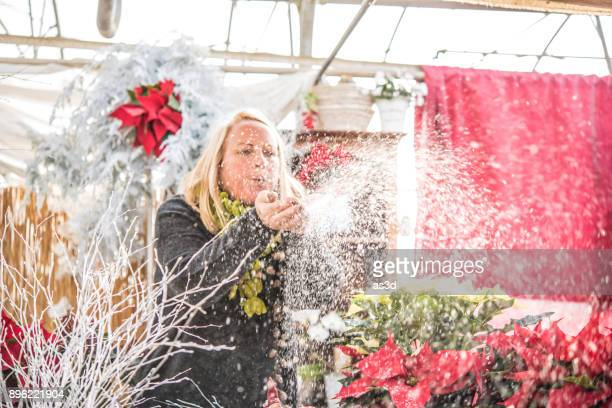 woman blowing artificial snow - fake snow stock pictures, royalty-free photos & images