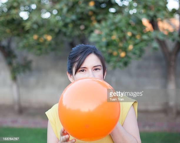 Woman blowing balloon