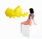 woman blowing bright yellow smoke