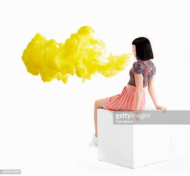woman blowing bright yellow smoke