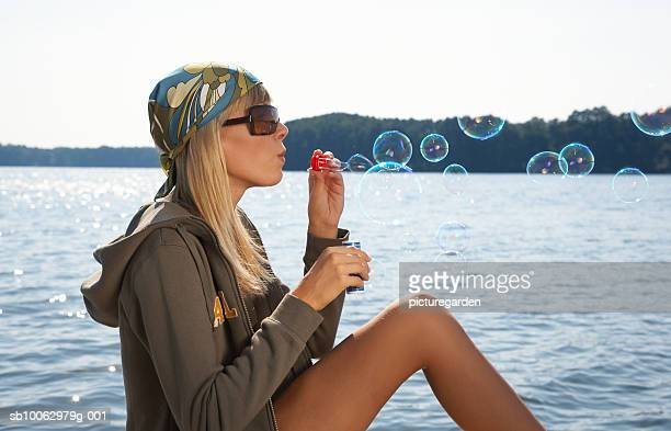 Woman blowing bubbles by lake, profile