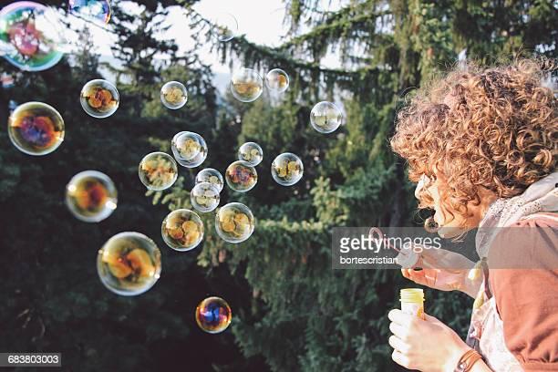 woman blowing bubbles from wand - bortes foto e immagini stock
