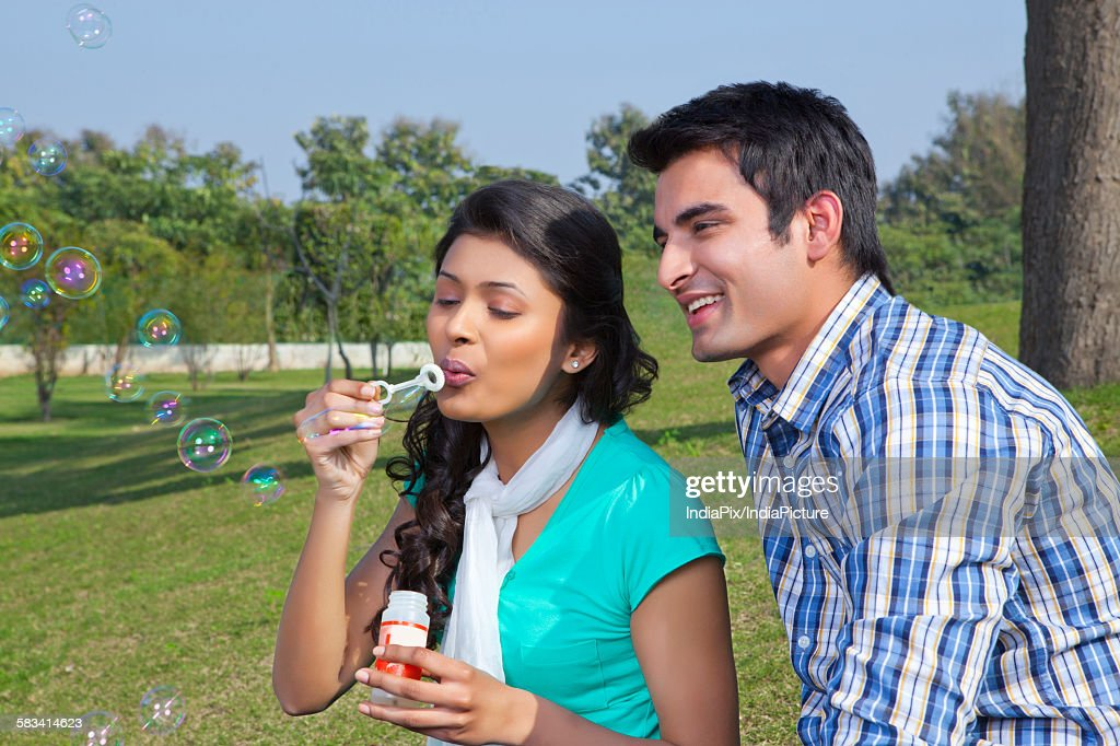 Woman blowing bubbles : Stock Photo