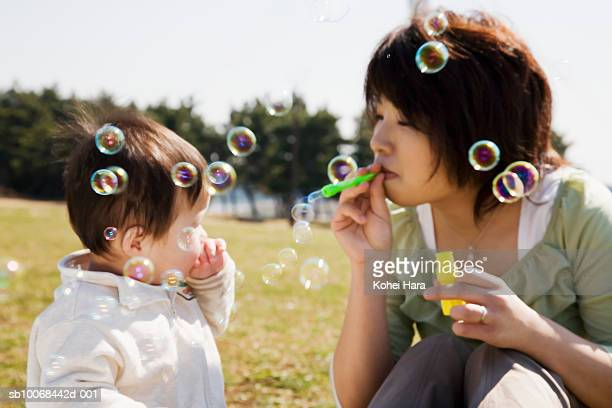 Woman blowing bubbles with son (6-11 months) in park