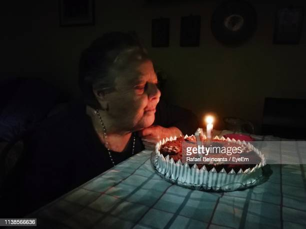 woman blowing burning candles on cake in the dark - candle in the dark imagens e fotografias de stock