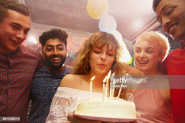 Woman blowing candles while celebrating birthday with friends at yard