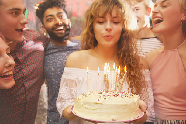 woman blowing candles while celebrating birthday with friends - best friend birthday cake stock pictures, royalty-free photos & images