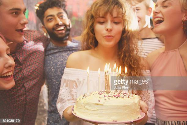 woman blowing candles while celebrating birthday with friends - 誕生日 ストックフォトと画像