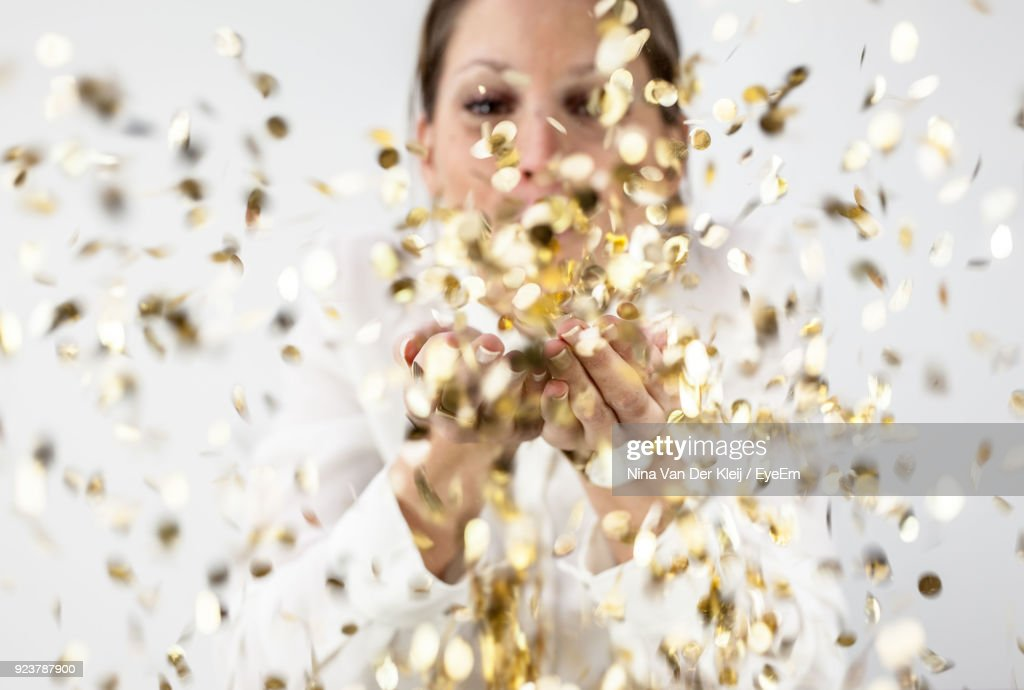 Woman Blowing Confetti Against White Background : Stockfoto