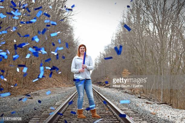 woman blowing confetti on railroad track - baum stock pictures, royalty-free photos & images