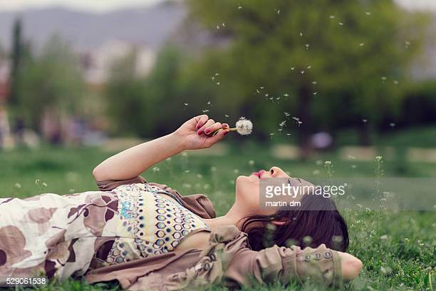 Donna che soffia di tarassaco nel parco con spazio per il testo
