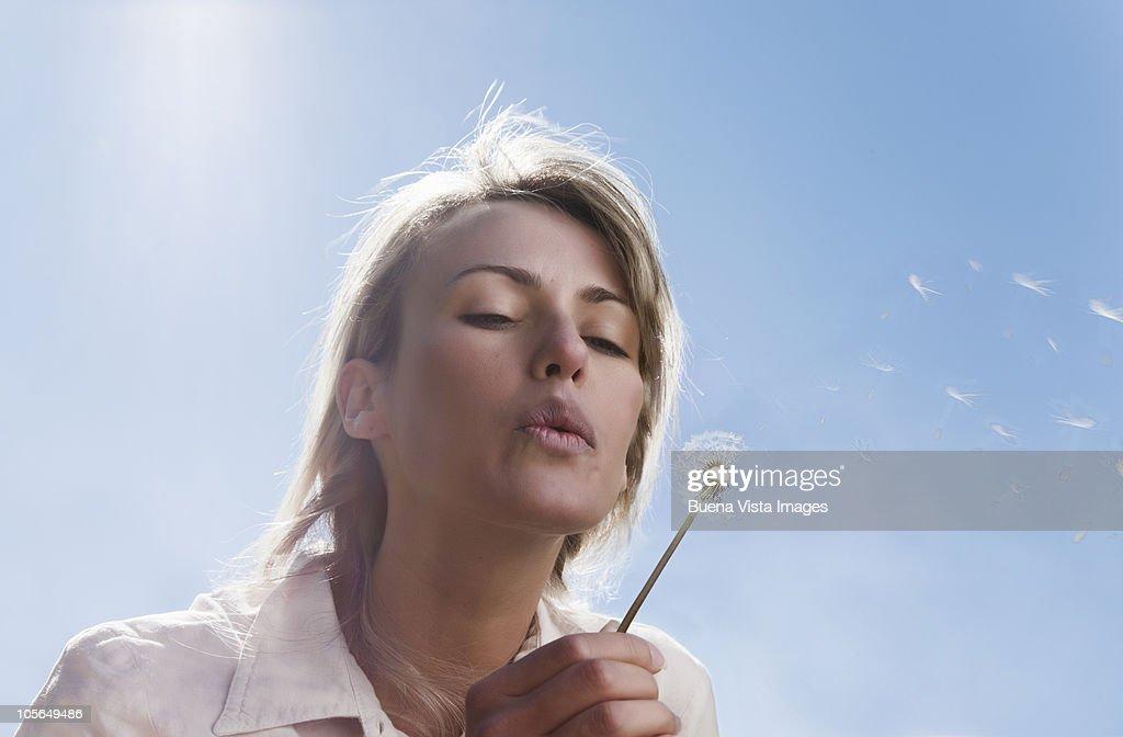 Woman blowing dandelion  : Stock Photo