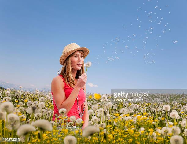 Woman blowing dandelions outdoors