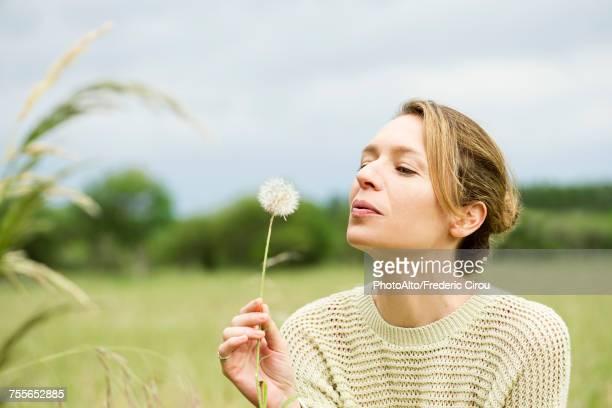 Woman blowing dried dandelion flower