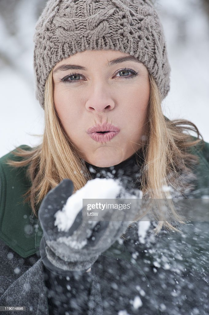 Woman blowing handful of snow : Stock Photo