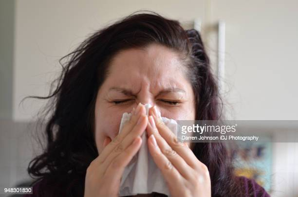 Woman blowing her nose hard into a tissue at home