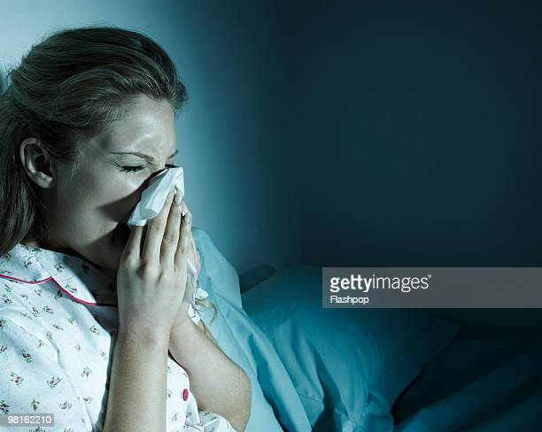 woman blowing her nose in bed - cold and flu stock pictures, royalty-free photos & images