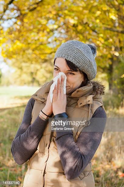 woman blowing her nose in park - stefanie grewel stock-fotos und bilder