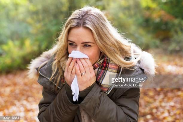 woman blowing her nose on a tissue - sonarse fotografías e imágenes de stock