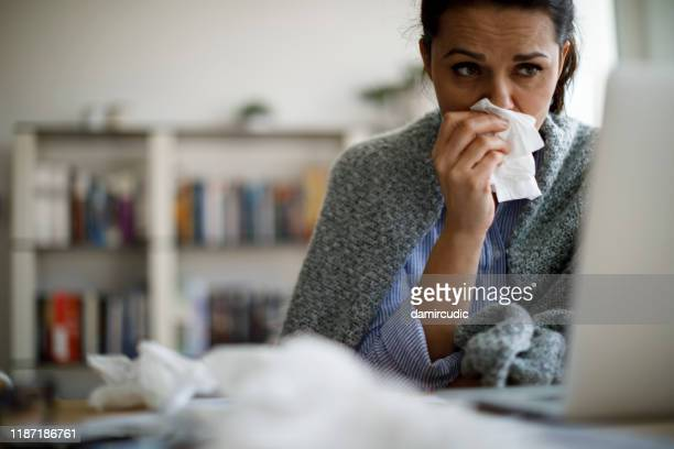 woman blowing her nose - cold virus stock pictures, royalty-free photos & images