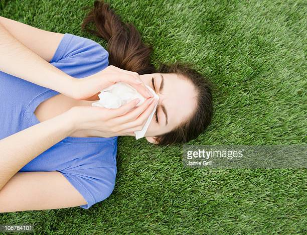 Woman blowing her nose while lying on grass