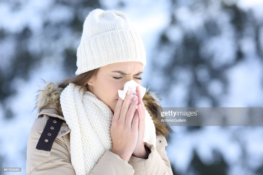 Woman blowing in a tissue in a cold snowy winter : Stock Photo