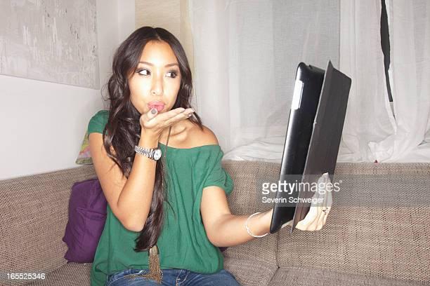 Woman blowing kiss at tablet computer