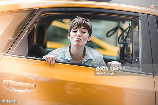 Woman blowing kiss from yellow taxi, New York, US
